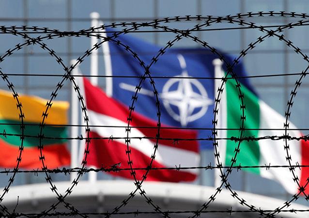 A bandeira da OTAN é vista através de arame farpado tremulando em frente à nova sede da aliança em Bruxelas, na Bélgica.