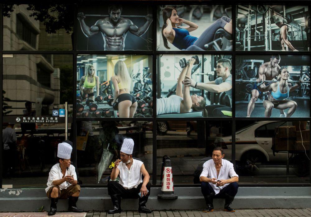 Três chefs de restaurante fazem uma pausa em frente a uma academia no centro de Xangai, em 4 de setembro de 2018