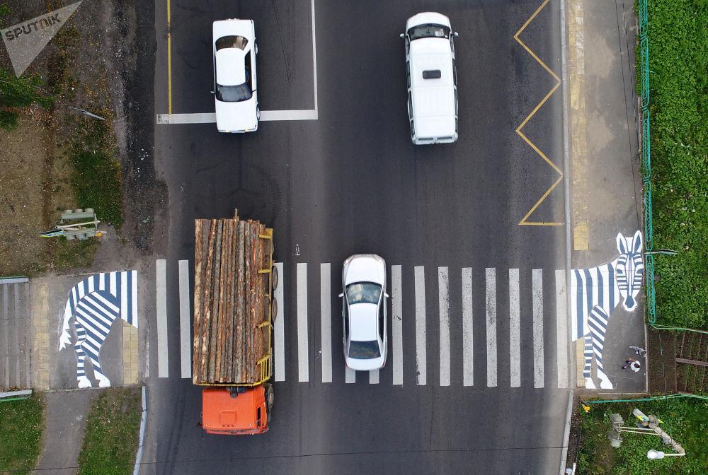 Pessoas esperam na faixa de pedestre enquanto os veículos conduzem ao longo da estrada no subúrbio de Krasnoyarsk, Rússia, em 30 de agosto de 2018