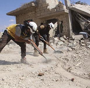 Capacetes Brancos limpando destroços de uma casa que foi atingida por um ataque aéreo do governo da Síria, em Idlib, 10 de setembro de 2010