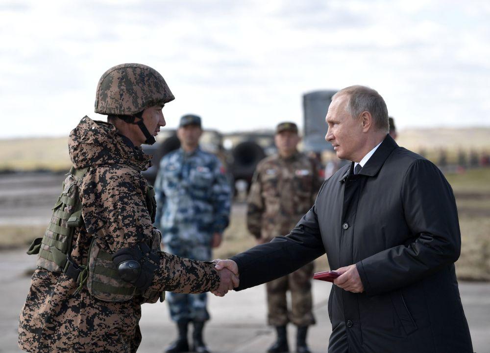 Presidente da Rússia Vladimir Putin apertando mão de um militar no polígono Tsugol