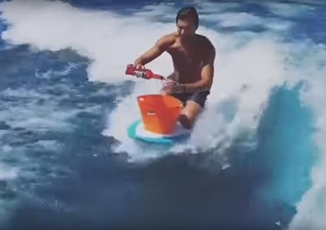 Homem surfa enquanto prepara drink