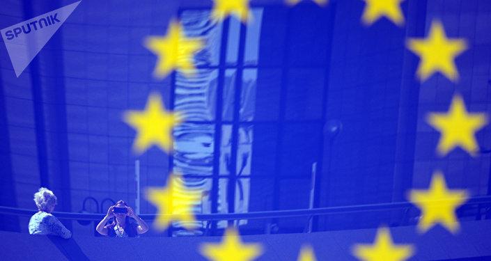 Turistas refletidos em um logotipo da UE