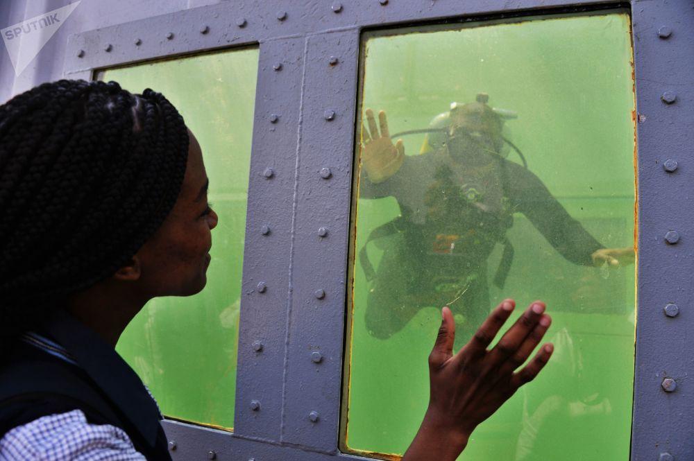 Visitante no estande de demonstração de equipamentos de mergulho na base da Força Aérea africana em Pretória