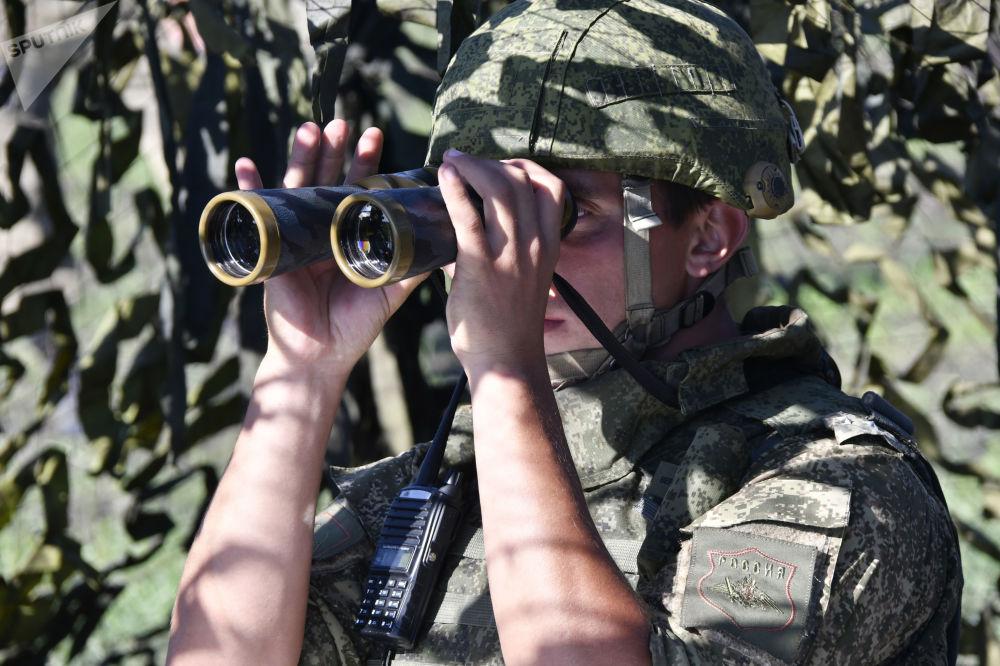 Militar em posição de observação durante exercício da artilharia tática no campo de treinamento de Molkino, em Krasnodar