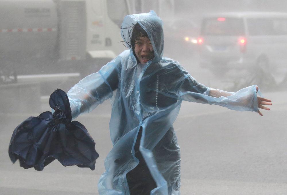 Mulher sob o aguaceiro provocado pelo tufão Shenzhen, na China