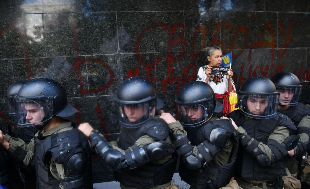 Mulher junto a agentes da polícia ucraniana em frente do Ministério Público da Ucrânia, em Kiev, durante um protesto de extrema-direita