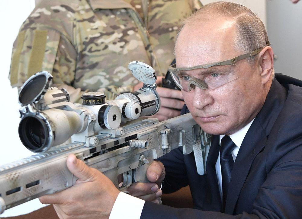Presidente russo, Vladimir Putin, dispara uma arma Kalashnikov durante uma visita ao centro do consórcio homônimo no parque Patriot, nos arredores de Moscou