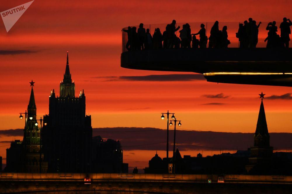 Visitantes do parque Zaryadie desfrutam da paisagem de Moscou ao anoitecer