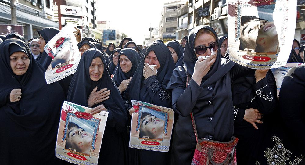Iranianas exibem imagem de menino de 4 anos, Mohammad Taha Eghdami, uma das vítimas do ataque terrorista na cidade de Ahvaz, no Irã, em 22 de setembro de 2018