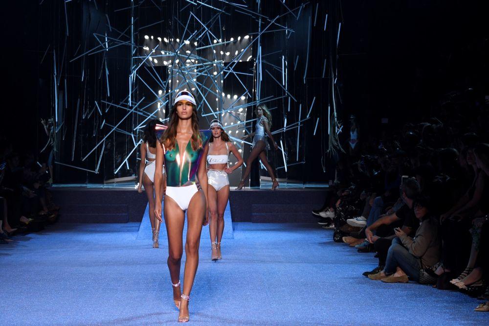 Modelos desfilam na passarela, sendo observadas por muitos espectadores famosos