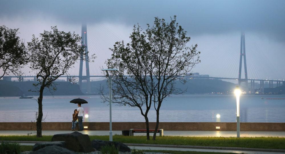 Jovens passeiam na beira do estreito Bósforo Oriental, na ilha de Russky em Vladivostok