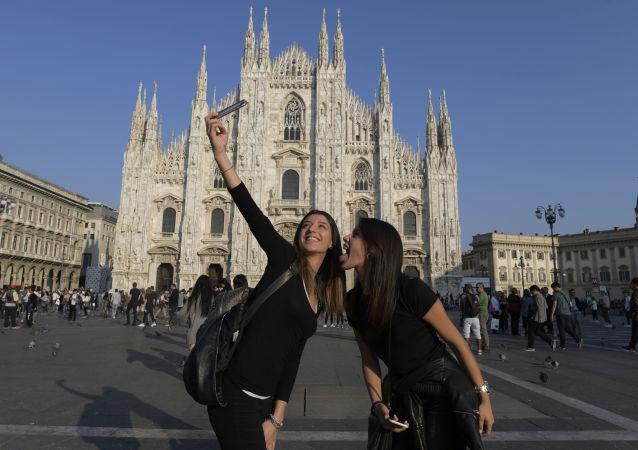 Turistas tiram selfie perto da Catedral de Milão, Itália