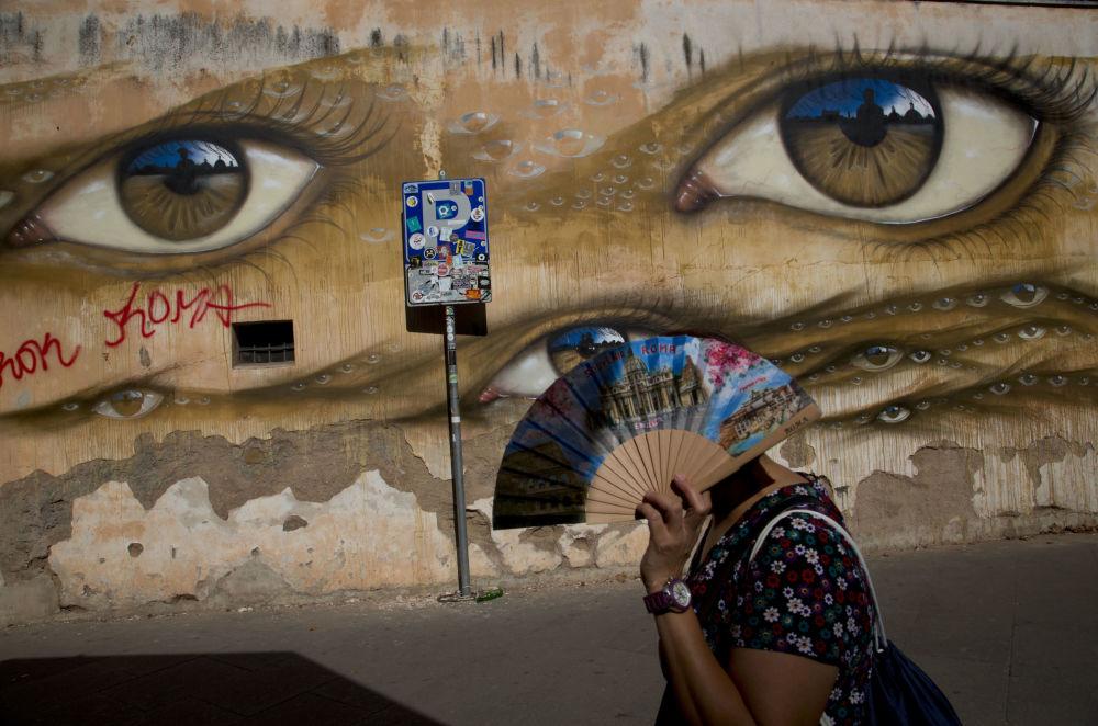 Mulher caminha junto ao mural do artista de rua britânico My Dog Sighs, no bairro de Trastevere, Roma.