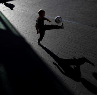 Criança jogando futebol perto do Royal Festival Hall, em Londres, antes da cerimônia de entrega do prêmio The Best FIFA.
