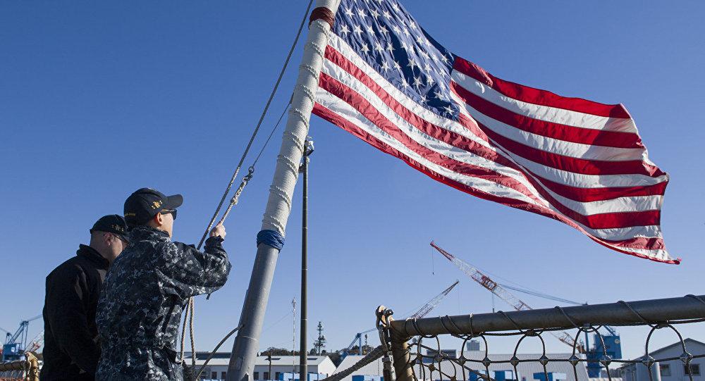 Marinheiros americanos designados para o destróier de classe Arleigh Burke, USS John S. McCain, abaixam o mastro enquanto o navio se dirige para uma patrulha de rotina na região Indo-Ásia-Pacífico