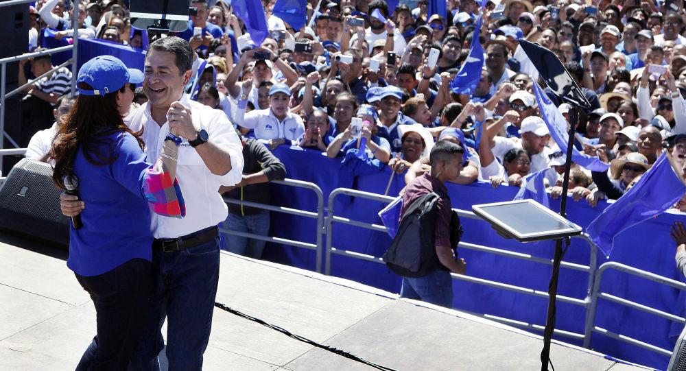 Presidente de Honduras, Juan Orlando Hernández, dança com sua mulher durante comício de campanha