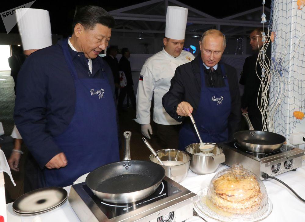O líder chinês Xi Jinping e o presidente russo Vladimir Putin mostram suas habilidades culinárias durante o Fórum Econômico Oriental em Vladivostok, na Rússia, 11 de setembro de 2018