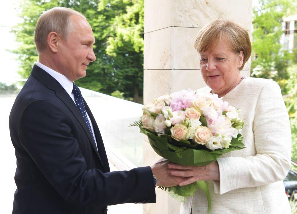 Vladimir Putin oferece um buquê de flores à chanceler da Alemanha, Angela Merkel, antes da reunião dos dois líderes em Sochi, na Rússia, 18 de maio de 2018