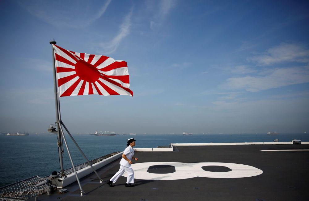 Japonesa que serve na Marinha do Japão corre pelo convés do porta-helicópteros Kaga