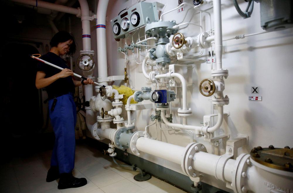 Mulher marinheira limpa tubos em um corredor do navio japonês Kaga