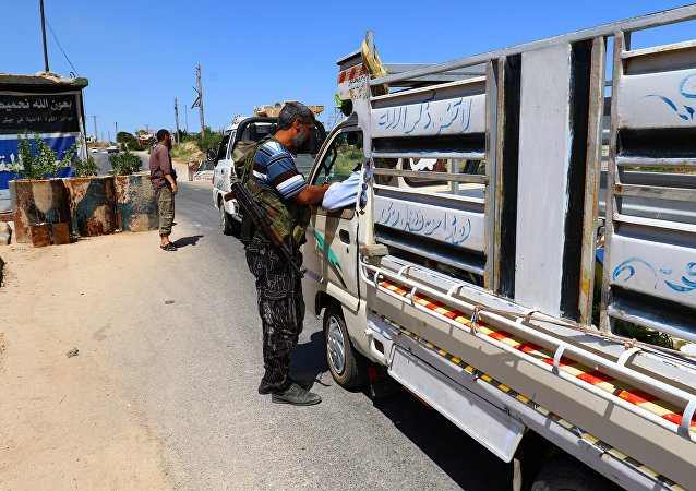 Membros de uma coalizão de grupos rebeldes chamada Jaish al Fateh, também conhecido como Exército Fatah, em um posto de controle na cidade de Idlib, na Síria.