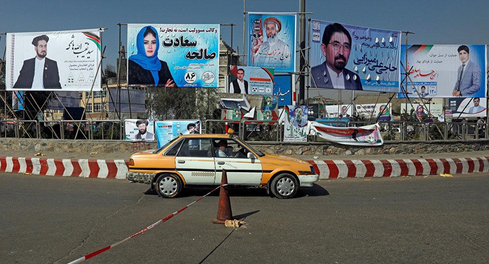 Um veículo circula em frente a cartazes eleitorais de candidatos parlamentares instalados durante o primeiro dia da campanha eleitoral em Cabul, Afeganistão.
