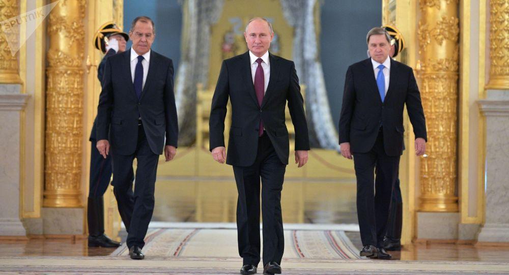 Presidente russo Vladimir Putin participa da cerimônia de entrega das credenciais de embaixadores estrangeiros no Palácio Estatal do Kremlin, junto com o chanceler Sergei Lavrov (à esquerda) e o assessor da presidência, Yuri Ushakov (à direita)