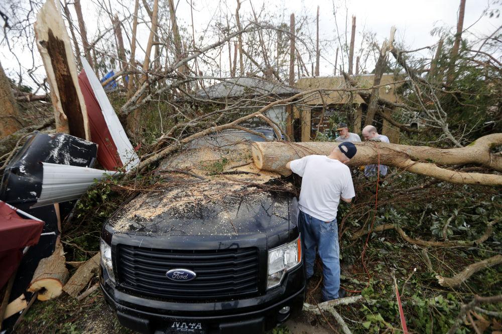 Pessoas serram árvores derrubadas pelo furacão Michael em Panama City, na Flórida