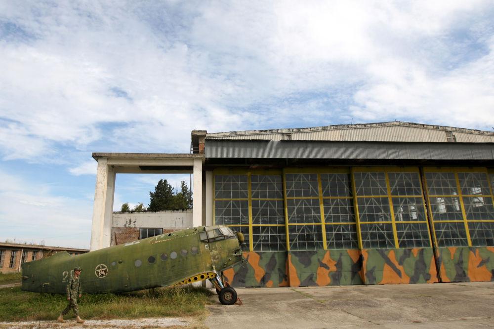 Militar da Força Aérea albanesa caminhando ao lado de um avião obsoleto An-2 na base aérea de Kucove
