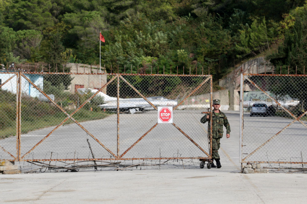 Militar albanês fechando os portões da base aérea de Kucove