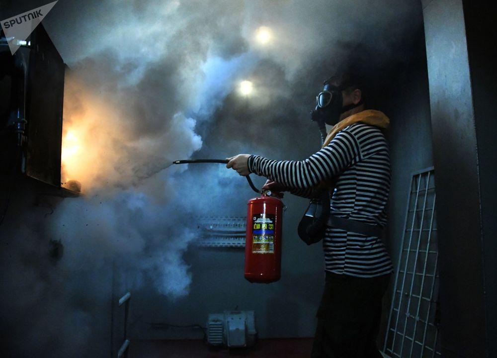 Marinheiro da Frota do Pacífico no compartimento de luta contra fogo durante exercícios em um centro de preparação na cidade russa de Vladivostok