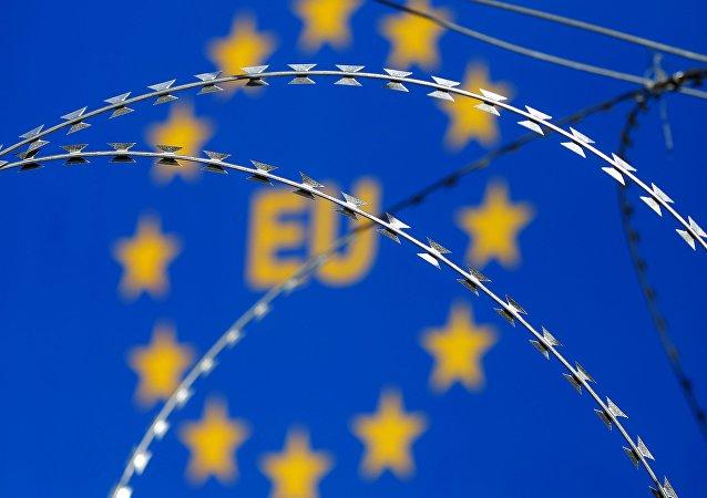 Arame farpado visto na frente da logo da União Europeia (UE)