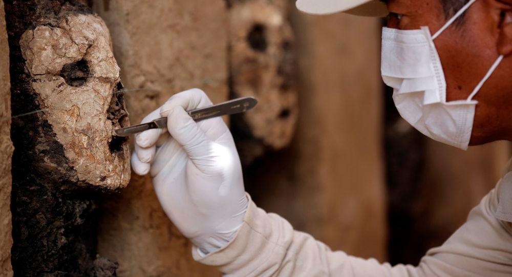 Arqueólogo escavando uma máscara de madeira da civilização Moche em Chan Chan, Peru