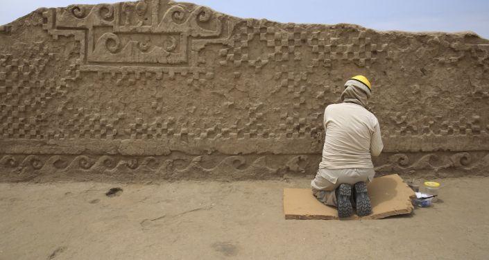 Arqueólogo durante a restauração do muro em Chan Chan, Peru