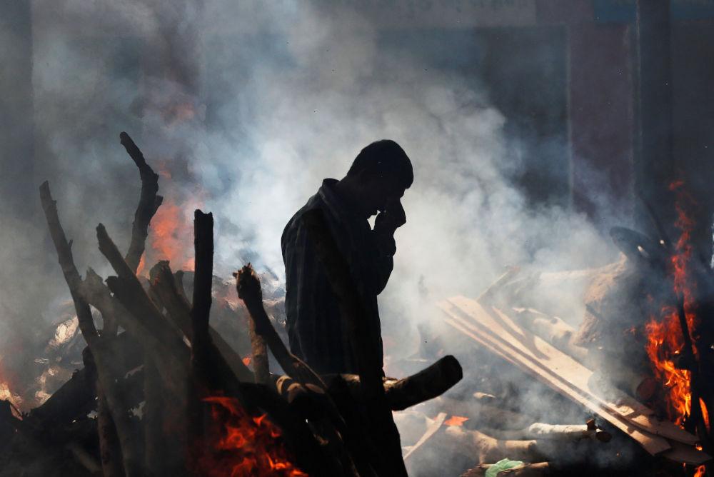 Homem chorando ao lado de pira funerária de um familiar morto ao ser atingido por um trem na Índia durante um festival