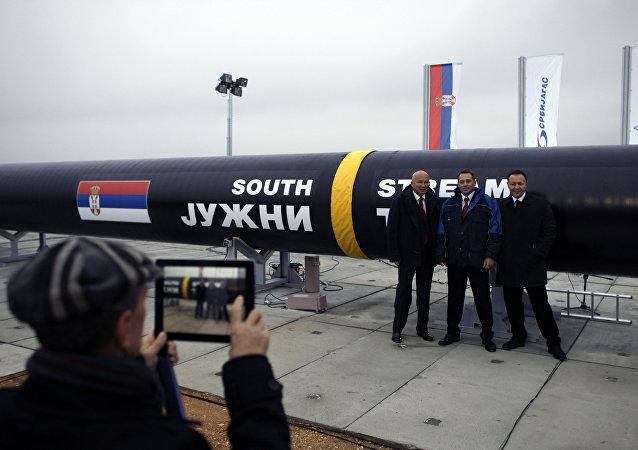Três homens tiram fotos ao lado da primeira seção do gasoduto da Gazprom South Stream, na cidade de Sajkas, a 80 quilômetros ao norte de Belgrado.