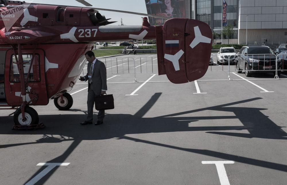 Visitante da exposição de helicópteros HeliRussia 2015 perto do helicóptero russo Ka-226T