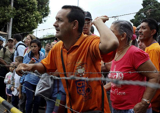 Pessoas perto do arame farpado da fronteira com a Colômbia, tentado passá-la pela ponte internacional Francisco de Paula Santander, em Ureña