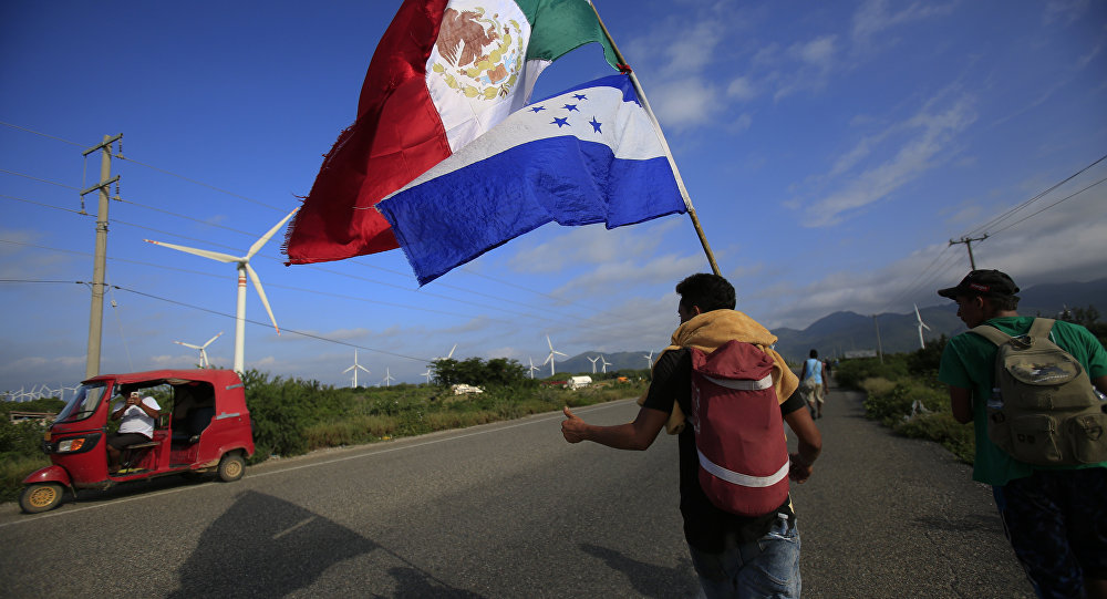 Um migrante carregando as bandeiras do México e de Honduras dá sinal de positivo para um piloto de moto que parou para tirar sua foto, enquanto uma caravana de milhares de pessoas da América Central espera alcançar os limites da fronteira dos EUA a partir de Juchitan, estado de Oaxaca, México.