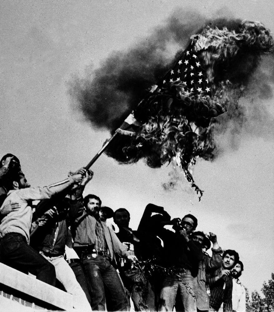 Manifestantes queimam a bandeira estadunidense no muro da embaixada dos EUA em Teerã na sequência da tomada de reféns em 4 de novembro, em 9 de novembro de 1979