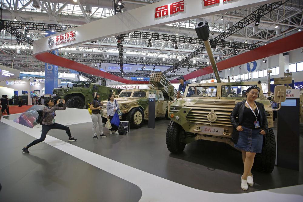 Visitantes tiram fotos junto a equipamentos militares na Exposição Internacional de Aviação & Aeroespacial da China 2018