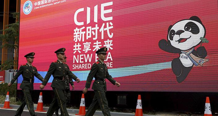 Policiais marcham em frente a uma propaganda da China International Import Expo durante a abertura da feira de negócios em Xangai, China.