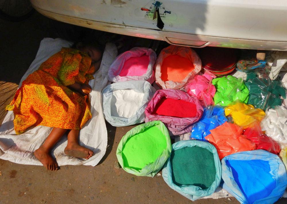 Criança dorme perto de sacos com pó colorido em um mercado em Nova Deli, na Índia