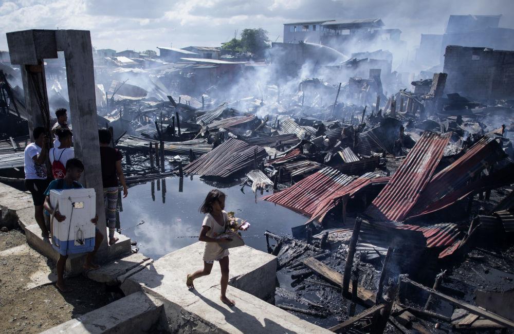 Menina passa pelas moradias destruídas pelo fogo em uma favela de Navotas, na Baía de Manila, nas Filipinas