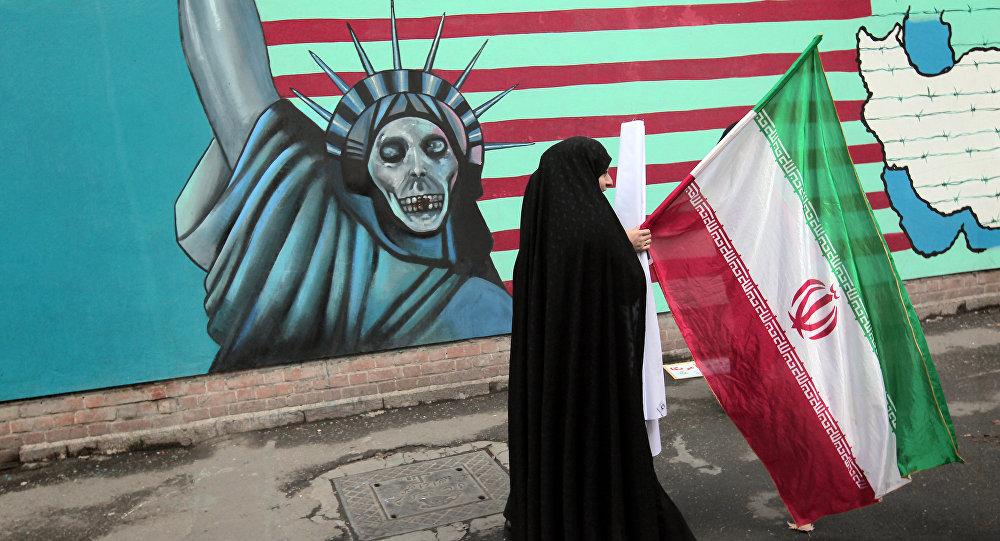 Mulher iraniana segura bandeira nacional enquanto passa por um muro representando a Estátua da Liberdade na parede da antiga embaixada dos EUA em Teerã (foto de arquivo)