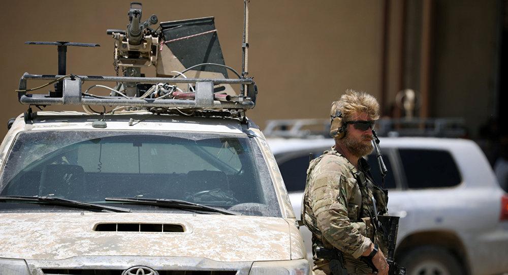 Soldados dos EUA segura uma arma enquanto mantém a guarda de um veículo blindado. A escolta faz parte da comitiva que acompanhou o enviado norte-americano para a coalizão internacional contra o Daesh, Brett McGurk, durante vistia à cidade de Tabqa, na Síria.