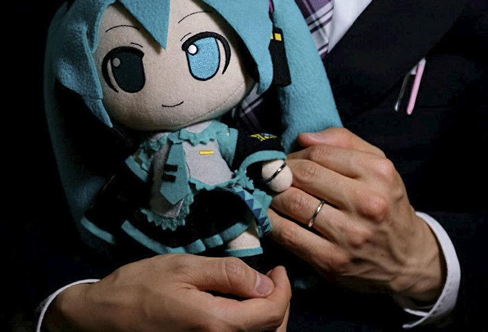 Akihiko Kondo com boneca da cantora virtual Hatsune Miku pondo suas alianças