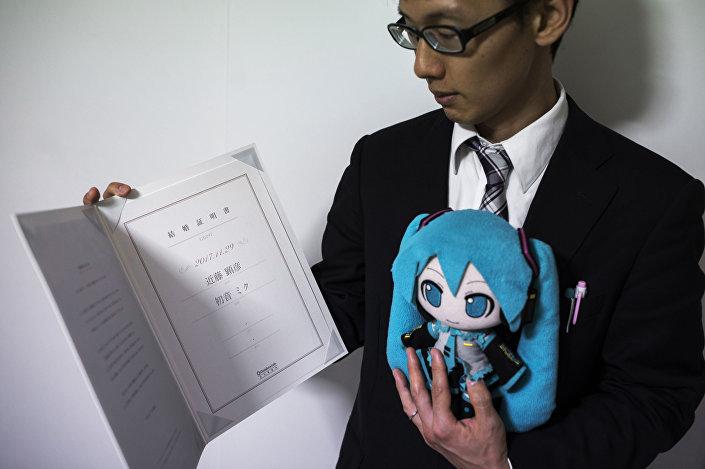Akihiko Kondo mostra a certidão de casamento, após se casar com a cantora virtual Hatsune Miku, segurando uma boneca dela