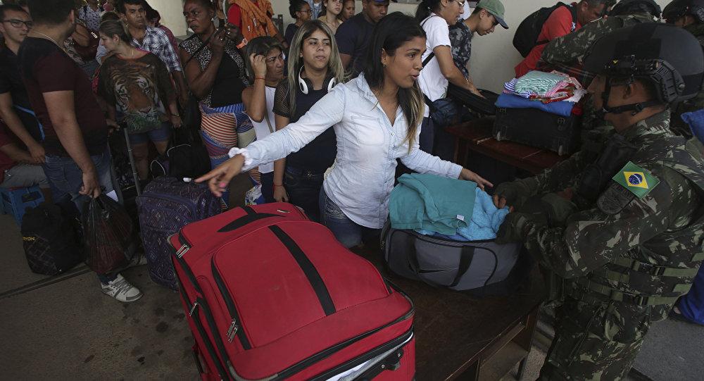 Uma mulher venezuelana fala com o soldado brasileiro que inspeciona malas na fronteira de Pacaraíma, em Roraima, um dos principais pontos de entrada de imigrantes venezuelanos no Brasil.